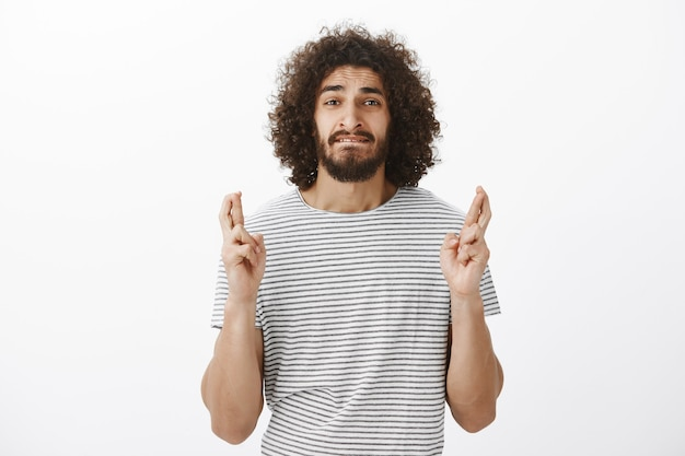 Retrato de um cara hispânico bonito preocupado com um penteado afro em uma camiseta listrada, mordendo o lábio ansiosamente e cruzando os dedos em esperança ou rezando, desejando que o sonho se tornasse realidade