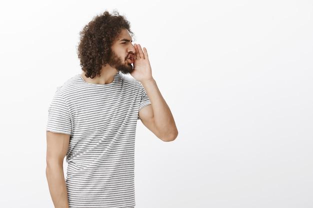 Retrato de um cara hispânico mal-educado irritado, virando à direita e segurando a palma da mão perto da boca enquanto grita palavrões em voz alta, franzindo a testa, sendo incomodado e irritado
