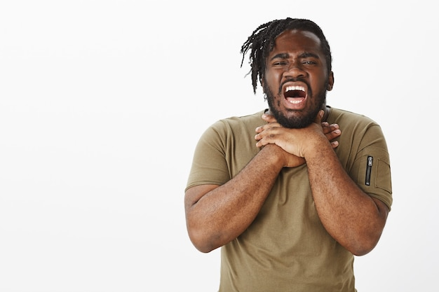 Retrato de um cara infeliz em uma camiseta marrom posando contra a parede branca