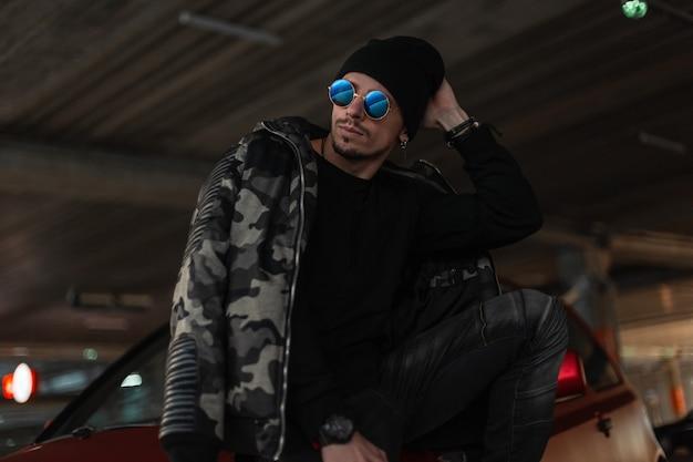 Retrato de um cara jovem e bonito hippie com óculos de sol legais em uma elegante jaqueta militar de inverno com um pulôver preto e um chapéu fica perto de um carro vermelho na cidade