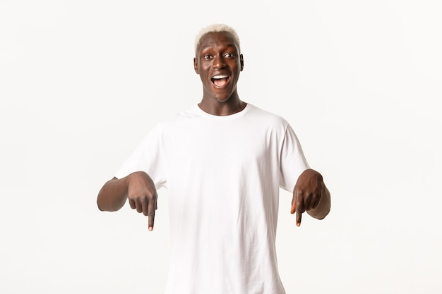 Retrato de um cara loiro afro-americano surpreso, mostrando o logotipo incrível, sorrindo divertido e apontando o dedo para baixo