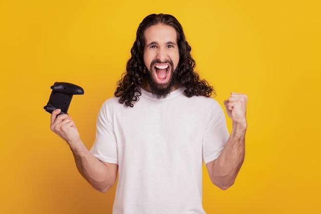 Retrato de um cara louco e positivo segurar o joystick para ganhar o grito do videogame em fundo amarelo