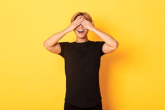 Retrato de um cara louro sorridente, divertido e animado, fechando os olhos com as palmas das mãos, esperando pela surpresa, em pé na parede amarela