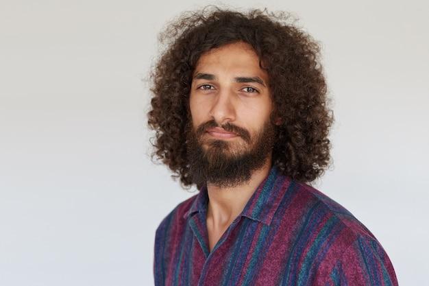 Retrato de um cara moreno atraente e encaracolado com uma barba exuberante, mantendo os lábios dobrados enquanto olha, posando com uma camisa listrada multicolorida