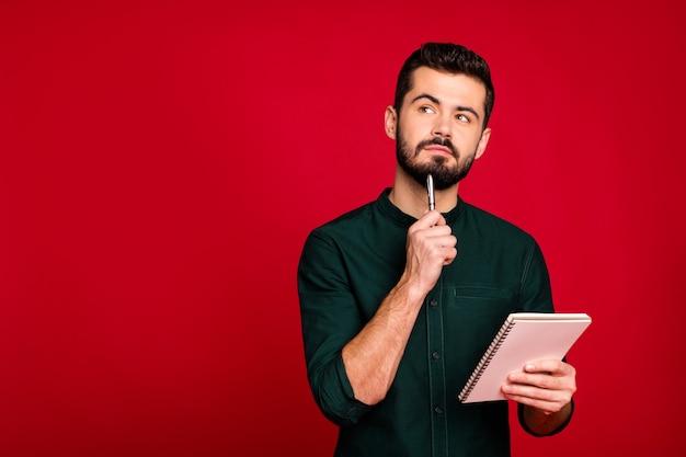 Retrato de um cara pensativo escreve um artigo em seu caderno, pensa pensamentos, olha copyspace usar roupas modernas