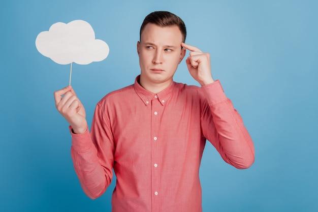 Retrato de um cara pensativo segurando uma vara, um balão de pensamento, pensando em ideias sobre um fundo azul