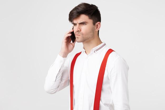 Retrato de um cara que fala ao telefone sentindo raiva, irritação, olhar voltado para o lado