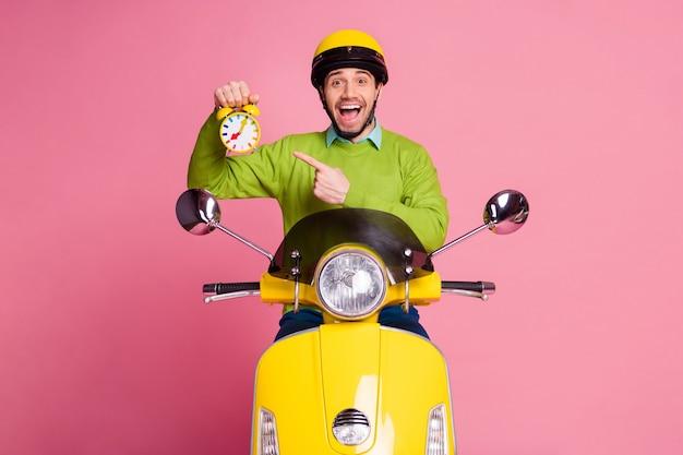 Retrato de um cara sentado em uma motocicleta, segurando, recomendando um despertador engraçado