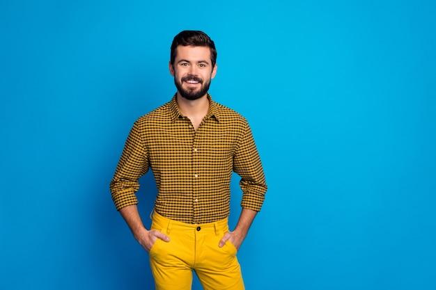 Retrato de um cara sincero satisfeito, descansar, relaxar, férias, colocar as mãos nos bolsos, vestir roupas elegantes isoladas sobre cores vibrantes