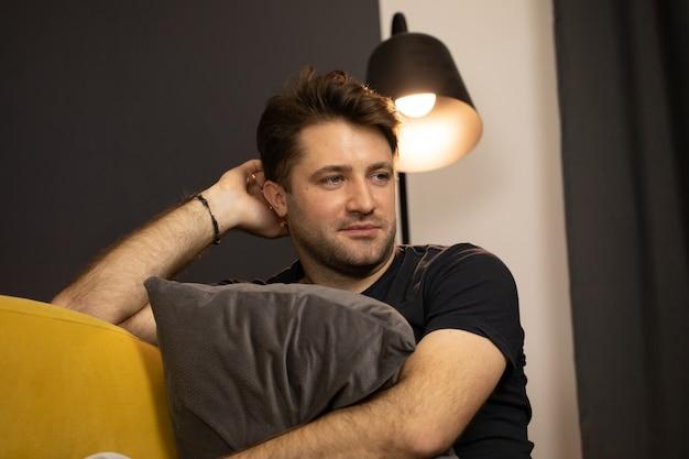 Retrato de um cara sorridente bonito com a barba por fazer sentado sob a lâmpada de spot abraçando o travesseiro