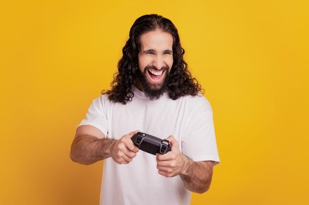 Retrato de um cara viciado bonito e alegre segurando o controle para jogar videogame em fundo amarelo