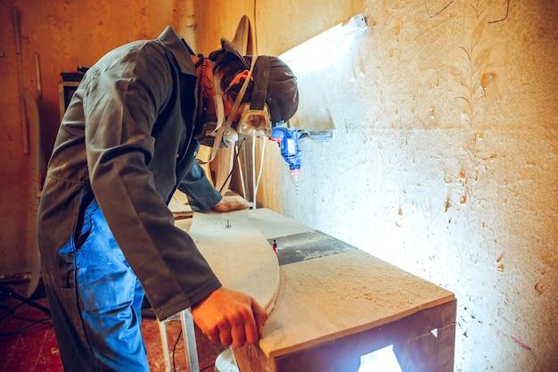 Retrato de um carpinteiro bonito trabalhando com um patim de madeira na oficina, vista de perfil