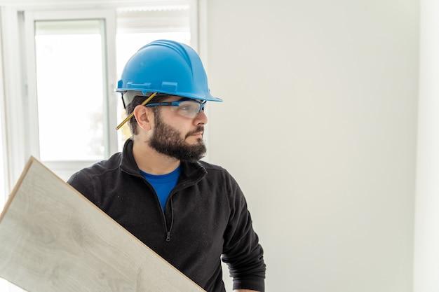 Retrato de um carpinteiro com um capacete protetor