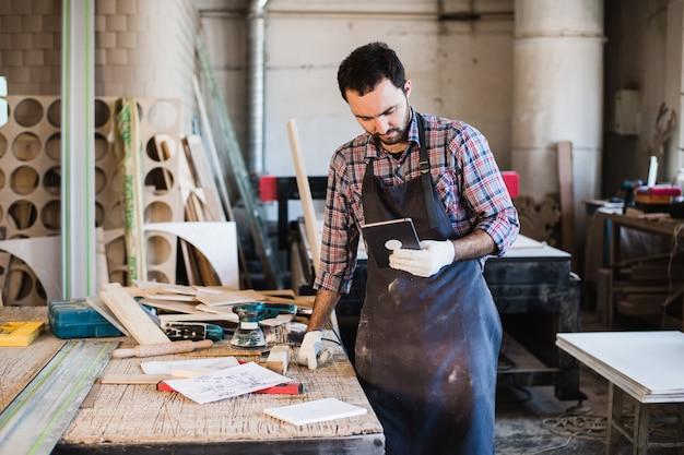 Retrato de um carpinteiro em pé em sua madeira e segurando o tablet digital