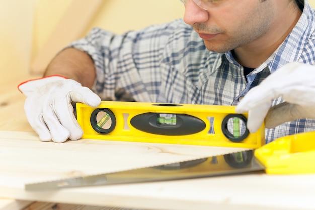 Retrato de um carpinteiro fazendo um trabalho de precisão em uma casa