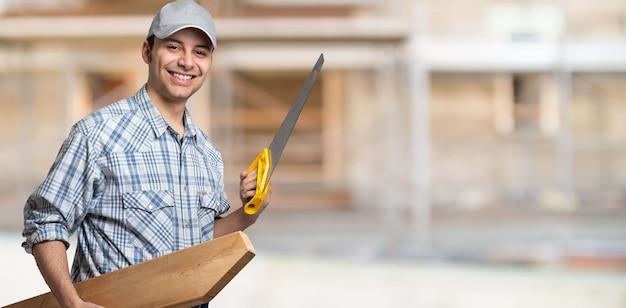 Retrato de um carpinteiro sorridente segurando uma prancha de madeira e uma serra em uma construção