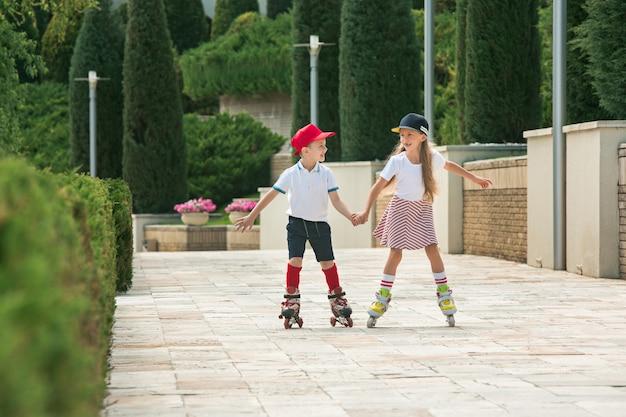 Retrato de um casal adolescente encantador patinando juntos de patins no parque. menino adolescente e menina caucasianos.
