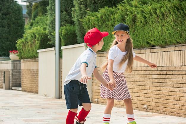 Retrato de um casal adolescente encantador patinando juntos de patins no parque.