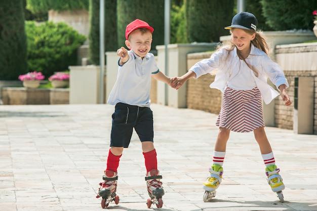 Retrato de um casal adolescente encantador patinando juntos em patins no parque.