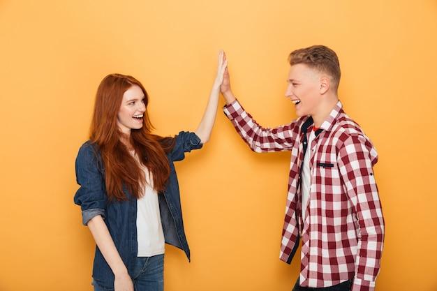 Retrato de um casal adolescente feliz dando mais cinco