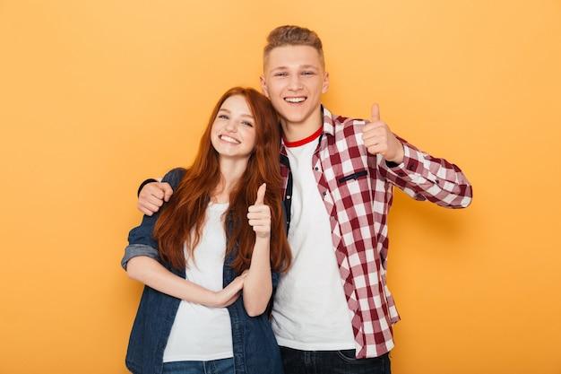 Retrato de um casal adolescente feliz mostrando o polegar para cima