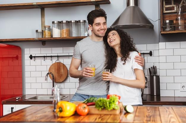 Retrato de um casal adorável, homem e mulher, cozinhando salat com legumes juntos, enquanto tomam café da manhã na cozinha de casa