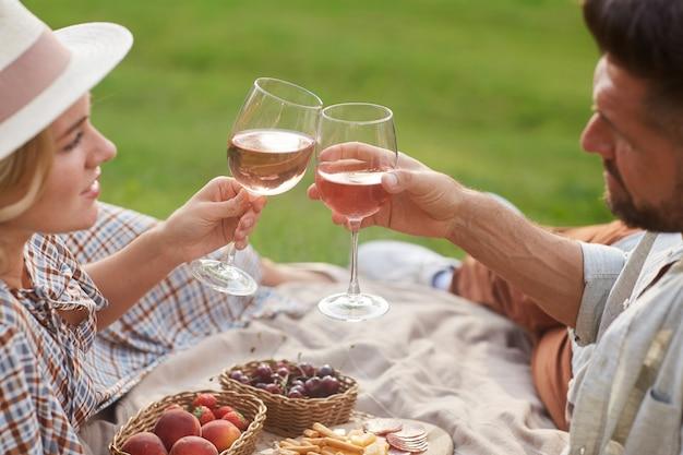 Retrato de um casal adulto apaixonado fazendo piquenique ao sol e tilintando taças de vinho durante um encontro romântico ao ar livre