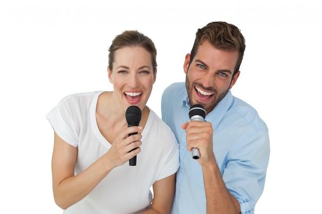 Retrato de um casal alegre cantando em microfones