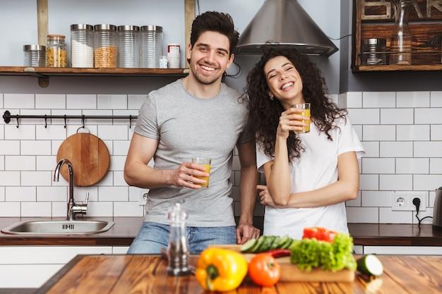 Retrato de um casal alegre, homem e mulher, cozinhando salat com legumes juntos, enquanto tomam café da manhã na cozinha de casa