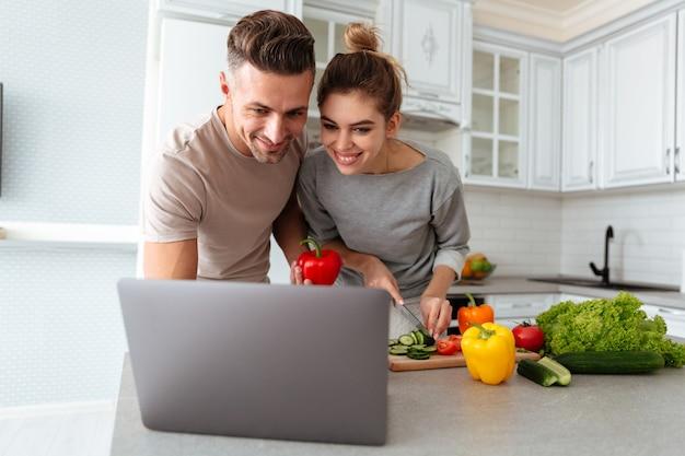 Retrato de um casal apaixonado alegre cozinhar salada juntos