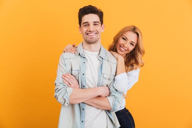 Retrato de um casal apaixonado, homem e mulher com roupas básicas, posando com um sorriso feliz, isolado sobre a parede amarela