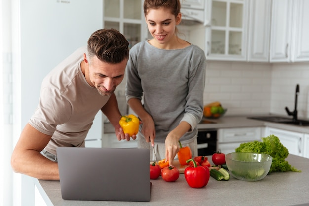 Retrato de um casal apaixonado sorridente cozinhar salada juntos