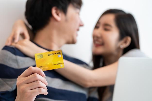 Retrato de um casal asiático alegre fazendo compras on-line na internet com o laptop