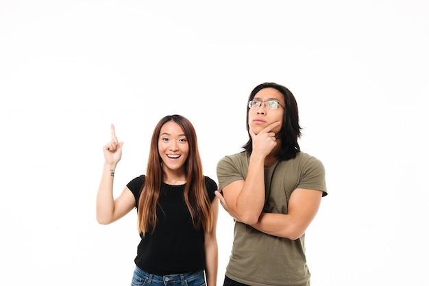 Retrato de um casal asiático sorridente pensativo, apontando o dedo para cima