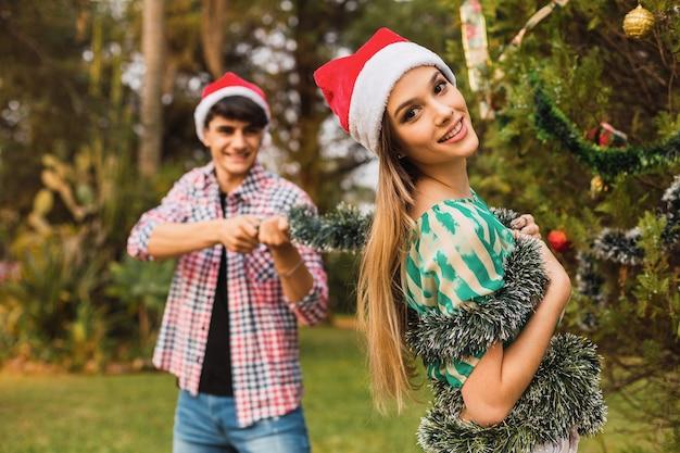 Retrato de um casal brincando enquanto decora a árvore de natal
