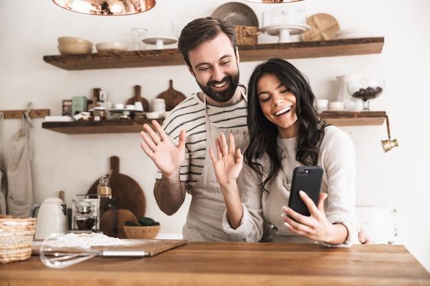 Retrato de um casal caucasiano, homem e mulher de 30 anos, usando aventais, se abraçando e segurando o smartphone enquanto cozinham na cozinha de casa