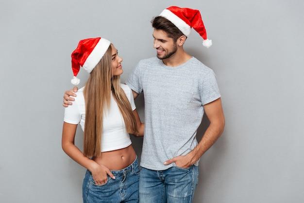 Retrato de um casal com chapéus de natal isolado parede cinza