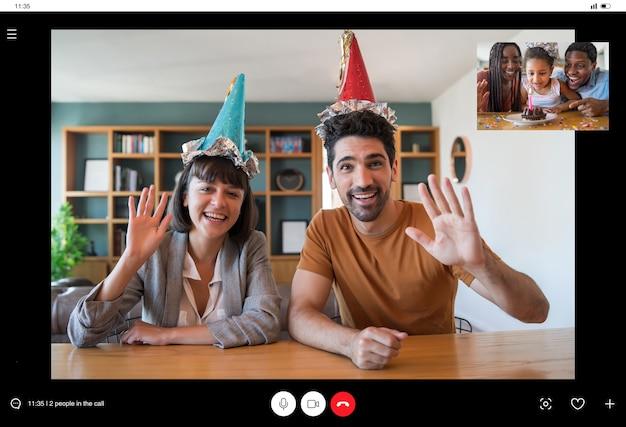Retrato de um casal comemorando aniversário em uma chamada de vídeo em casa.
