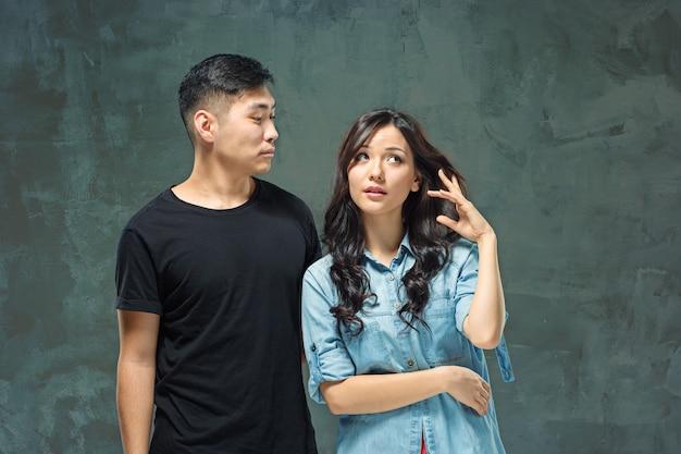 Retrato de um casal coreano sorridente em um cinza