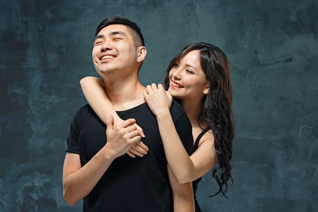 Retrato de um casal coreano sorridente em um estúdio cinza