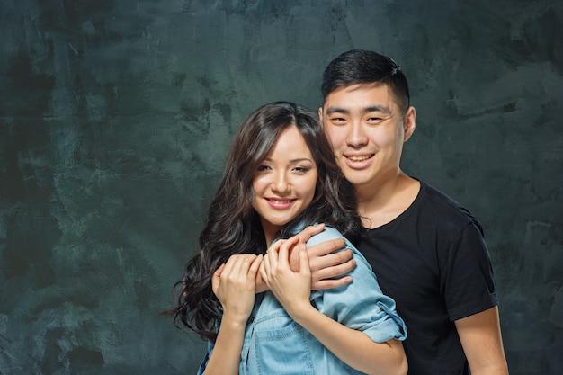 Retrato de um casal coreano sorridente em um fundo cinza de estúdio
