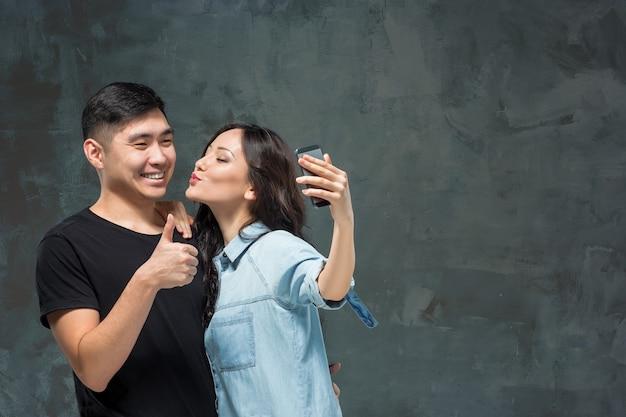 Retrato de um casal coreano sorridente fazendo uma selfie em um fundo cinza de estúdio