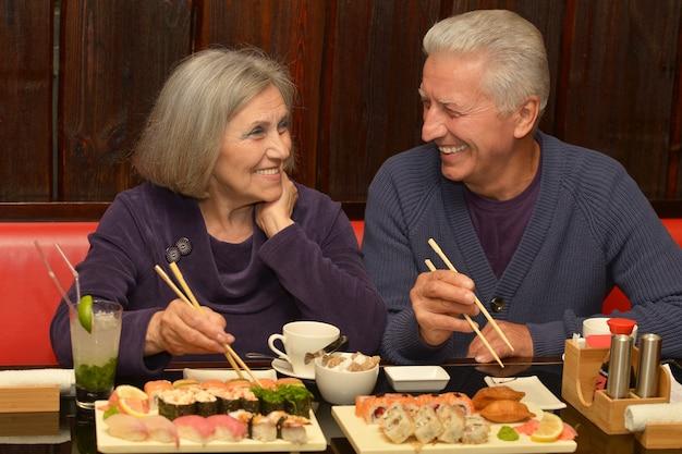 Retrato de um casal de idosos comendo sushi em um café