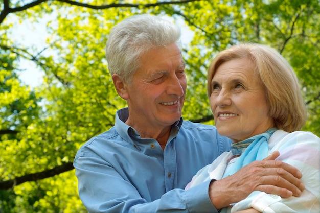 Retrato de um casal de idosos descansando em um parque de outono