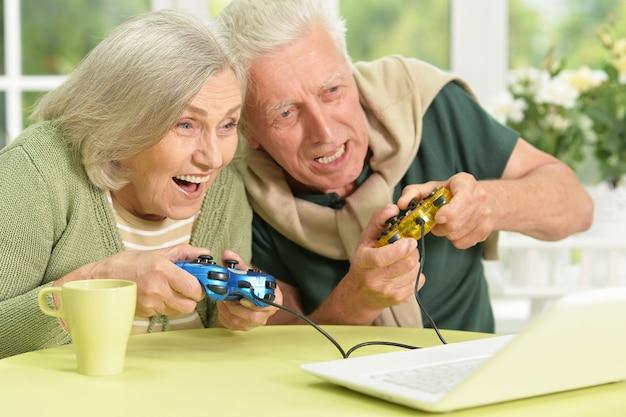Retrato de um casal de idosos feliz jogando videogame