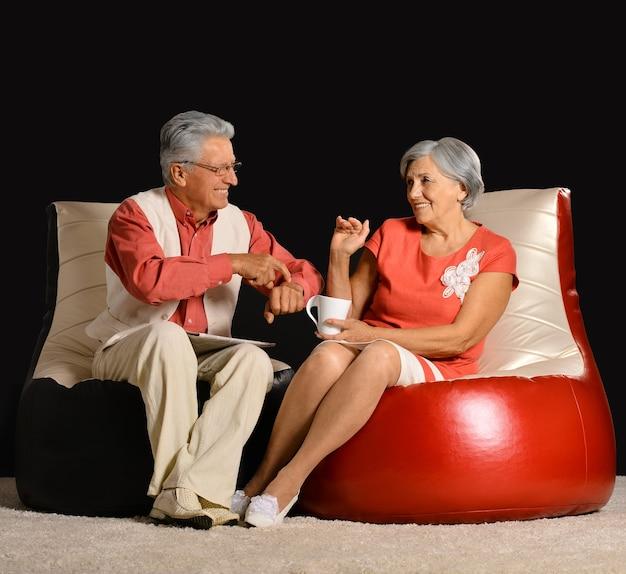 Retrato de um casal de idosos feliz sentado em poltronas