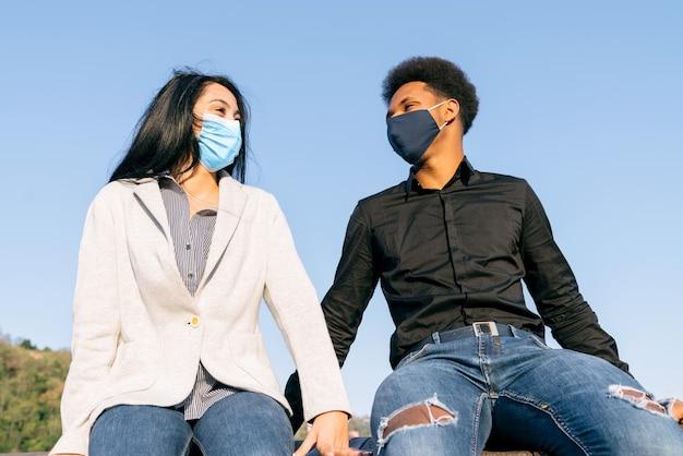Retrato de um casal de jovens amigos sentados em uma cidade na rua com um céu azul feliz com máscaras devido à pandemia de coronavírus covid-19