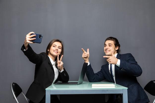 Retrato de um casal de negócios jovem feliz itting na mesa de escritório, vestindo ternos tomando uma selfie isolada