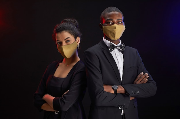 Retrato de um casal de raça mista elegante usando máscaras enquanto posa contra um fundo preto na festa, copie o espaço da cintura para cima