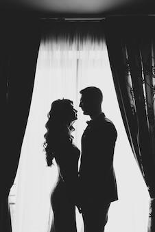 Retrato de um casal de silhueta romântica do noivo e noiva na janela